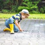 Kleiner Junge, der eine Zugmaschine mit Kreide im Sommer malt Lizenzfreie Stockbilder