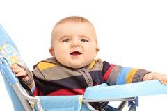 Kleiner Junge, der in einem Kinderwagen sitzt Stockbild