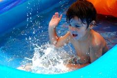 Kleiner Junge, der in einem Pool spritzt Stockfoto