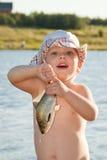 Kleiner Junge, der einen Fisch hält Stockbilder