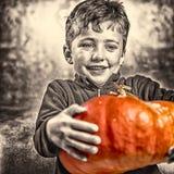 Kleiner Junge, der einen großen orange Kürbis hält Ein großes Spinnenweb vor einem sonderbaren hellen Mond Stockfotos