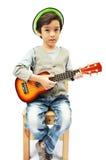 Kleiner Junge, der einen Musiker mit Ukulele vortäuscht lizenzfreie stockbilder