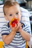 Kleiner Junge, der einen Pfirsich isst Stockbild