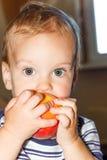 Kleiner Junge, der einen Pfirsich isst Stockfotografie