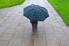 Kleiner Junge, der einen Regenschirm anhält Lizenzfreie Stockbilder