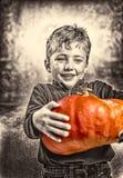 Kleiner Junge, der einen schweren Kürbis hält Ein großes Spinnenweb vor einem sonderbaren hellen Mond Stockfoto