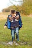Kleiner Junge, der in einer Pfütze auf dem Gebiet spritzt Stockfotos