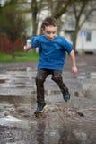 Kleiner Junge, der in einer Schlammpfütze spritzt, Lizenzfreie Stockfotografie