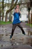 Kleiner Junge, der in einer Schlammpfütze spritzt, Lizenzfreies Stockbild
