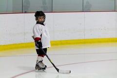 Kleiner Junge, der Eis-Hockey spielt Stockfoto