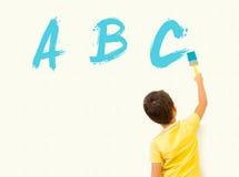 Kleiner Junge, der Englisch und paintng ABC auf der Wand lernt stockbilder