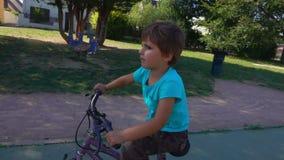 Kleiner Junge, der Fahrrad in einem Park fährt stock video
