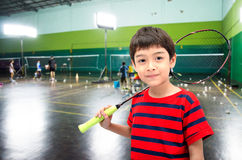 Kleiner Junge, der Federballschläger in der Trainingsklasse nimmt Stockbild