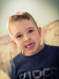Kleiner Junge, der fehlende Zähne zeigt Stockbild