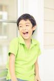 Kleiner Junge, der am Fenster mit glücklichem Gesichtsporträt sitzt Stockfotos