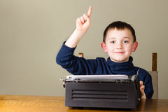 Kleiner Junge, der Finger, alte Weinleseschreibmaschine anhebt Stockbild