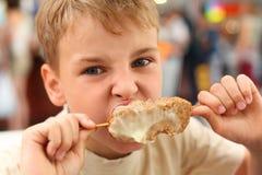Kleiner Junge, der Fleisch auf Steuerknüppel isst Stockbild
