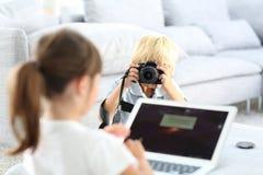Kleiner Junge, der Foto des kleinen Mädchens auf Laptop macht Lizenzfreie Stockfotos