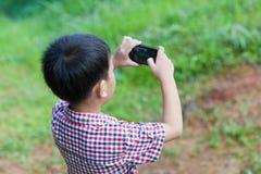 Kleiner Junge, der Fotos durch Digitalkamera auf Smartphone macht Stockbild