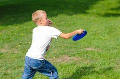Kleiner Junge, der Frisbee spielt Stockfotos