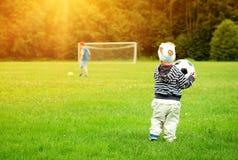 Kleiner Junge, der Fußball auf dem Feld mit Toren spielt Lizenzfreies Stockbild