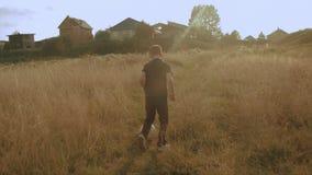 Kleiner Junge, der Fußball auf dem Gebiet spielt Kind, das durch Wiese mit einem Ball läuft Landschaft und Wald stock footage