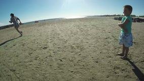 Kleiner Junge, der Fußball auf dem Strand spielt stock footage