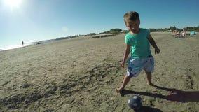 Kleiner Junge, der Fußball auf dem Strand spielt stock video footage