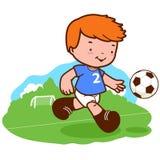 Kleiner Junge, der Fußball spielt Lizenzfreie Stockbilder