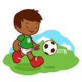 Kleiner Junge, der Fußball spielt Lizenzfreie Stockfotos