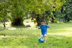 Kleiner Junge, der Fußball spielt Stockfotografie