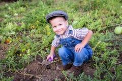 Kleiner Junge, der in Garten gräbt Stockfotografie