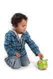 Kleiner Junge, der Geld in eine piggy Querneigung steckt Stockfoto