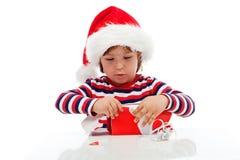 Kleiner Junge, der Geschenk auspackt Stockbild