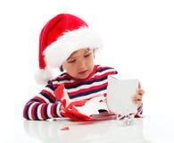 Kleiner Junge, der Geschenk auspackt Stockbilder