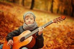 Kleiner Junge, der Gitarre auf Naturhintergrund, Herbsttag spielt Children& x27; s-Interesse an der Musik Stockbild