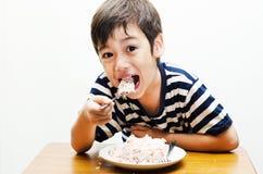 Kleiner Junge, der glückliches Gesicht des Reises isst Stockfoto