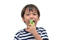 Kleiner Junge, der grünes Gemüse für Gesundheit isst stockfoto