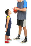 Kleiner Junge, der großen Mann bittet, Basketball zu spielen Lizenzfreie Stockbilder