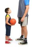 Kleiner Junge, der großen Mann bittet, Basketball zu spielen Stockfoto