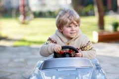 Kleiner Junge, der großes Spielzeugauto, draußen fährt Stockfotografie