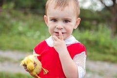 Kleiner Junge, der Hände eines Entleins hält und die Kamera untersucht Lizenzfreie Stockbilder