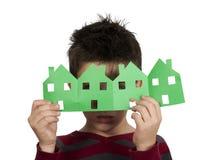 Kleiner Junge, der Häuser gemacht vom Papier hält Stockbild
