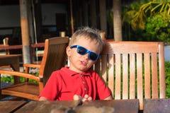 Kleiner Junge, der in hölzernes Café wartet Stockbilder