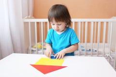 Kleiner Junge, der Haus aus Papierdetails konstruiert Lizenzfreies Stockbild