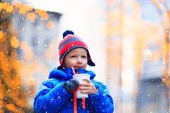 Kleiner Junge, der heißes Getränk im kalten Stadtwinter hat Stockbild