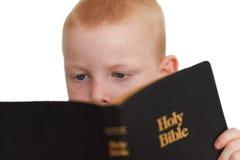 Kleiner Junge, der heilige Bibel liest Stockfoto