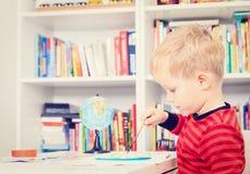 Kleiner Junge, der Heimarbeit tut Lizenzfreie Stockfotografie