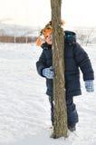 Kleiner Junge, der hinter einem Baumstamm schmollt und sich versteckt Lizenzfreie Stockbilder