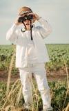 Kleiner Junge, der im Ackerland unter Verwendung der Ferngläser steht Lizenzfreie Stockfotografie